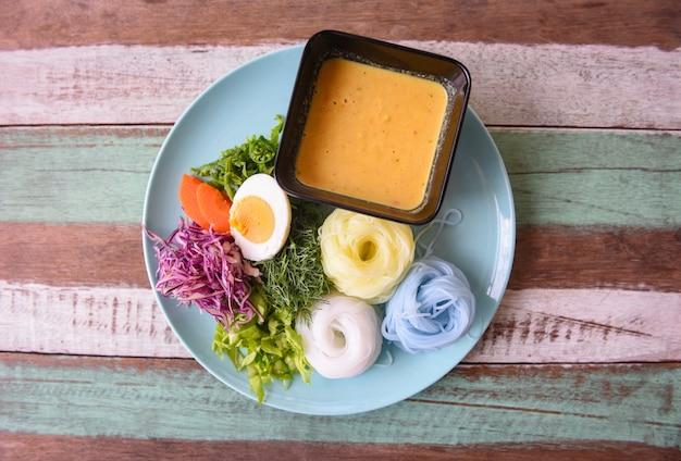 タイ料理のおいしくて美しい食べ物。カラフルなライスヌードルまたはタイライス春雨麺と魚カニのカレースープソースと野菜のプレート木製テーブル Premium写真