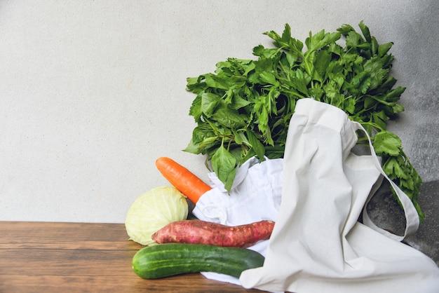 Нулевые отходы используют меньше пластика / свежие овощи органические в эко-хлопчатобумажных мешках на деревянном столе Premium Фотографии