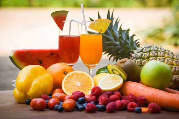 トロピカルフルーツのカラフルで新鮮な夏のジュースガラス健康食品のセット/熟したフルーツの混合 Premium写真