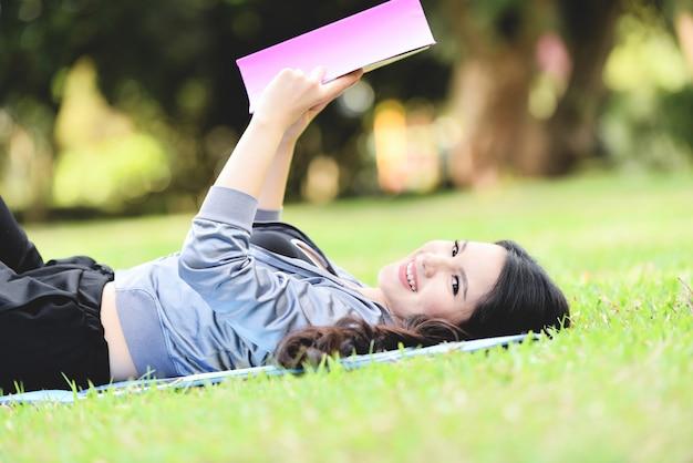 本を読んで、庭の公園で屋外の芝生のフィールドに横になっている若い女の子の笑顔幸せなアジア女性 Premium写真