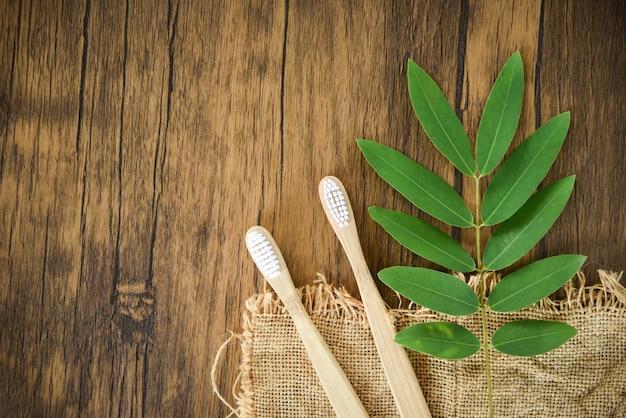 竹製の歯ブラシと緑の葉 - 無駄のないバスルーム Premium写真