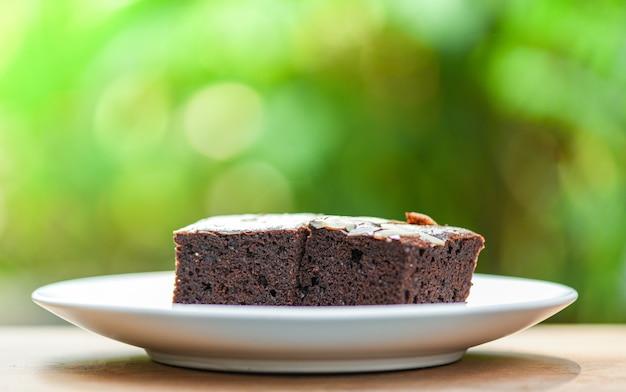 テーブルの上のブラウニーケーキ/木と自然の緑のナットとチョコレートケーキのスライス Premium写真