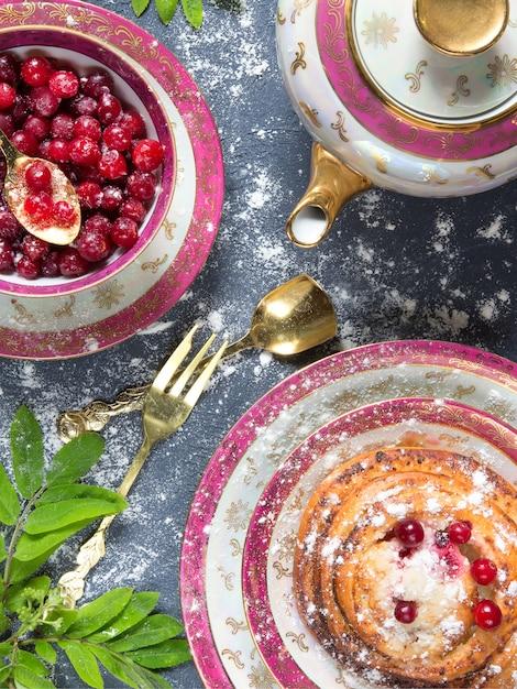 クランベリーと皿の上のジャムと木製の背景にナプキンのおいしいパンケーキのスタック Premium写真