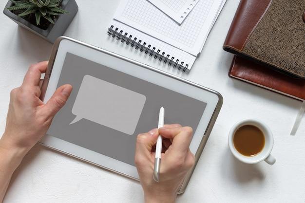 デジタルタブレットの指を使用して手作業机の上の空白の画面 Premium写真