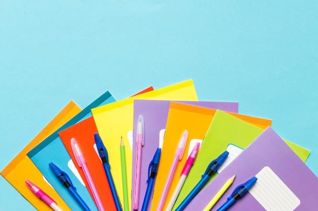 学校、ノート、ペン、青の背景に男子学生の職場の鉛筆用アクセサリー Premium写真