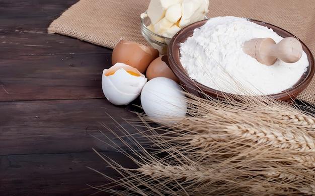 小麦と卵のヴィンテージの木の板の食べ物や飲み物のコンセプトにバターの小麦粉の卵をボウルします。 Premium写真