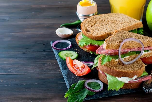 サンドイッチ、卵、カップコーヒー、朝食用ジュースのグラス Premium写真