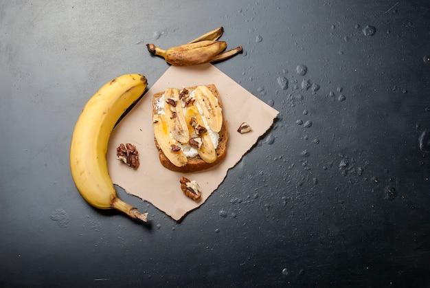 バナナ、ナッツ、チョコレート、黒いテーブルの上のおいしい甘いサンドイッチ Premium写真