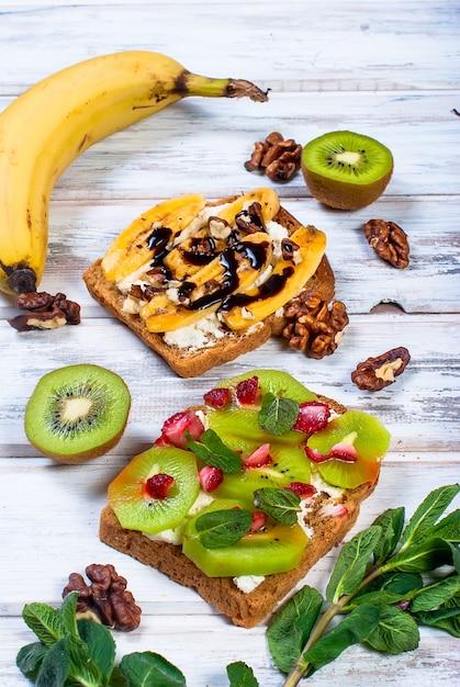 バナナ、ナッツ、チョコレート、木製テーブルの上のおいしい甘いサンドイッチ Premium写真