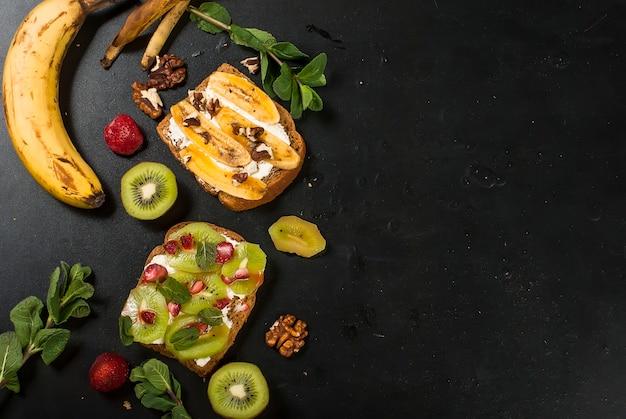 黒のバナナ、ナッツ、チョコレート、キウイ、イチゴ、ミントのおいしい甘いサンドイッチ Premium写真