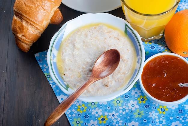バター、クロワッサン、コーヒー入りのオートミールで健康的な朝食 Premium写真