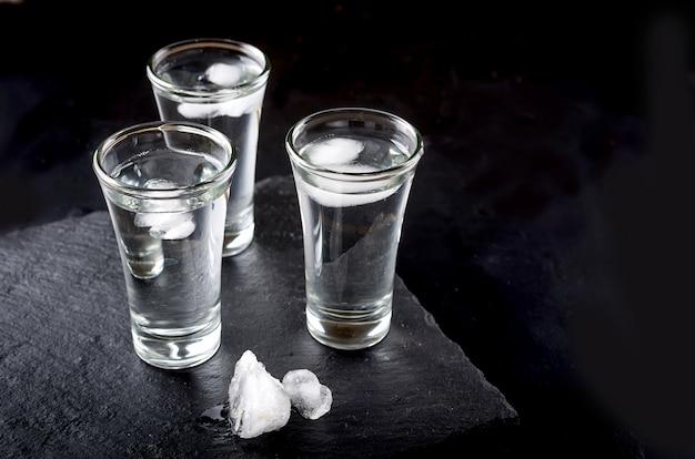 Водка на черном столе Premium Фотографии