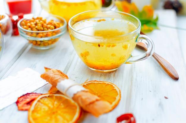 ガラスのカップとティーポットとフルーツのパスティーユの海クロウメモドキ茶 Premium写真