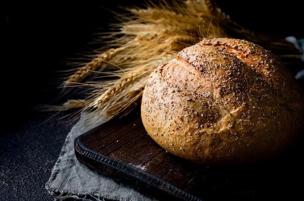 Буханка хлеба на черном столе Premium Фотографии