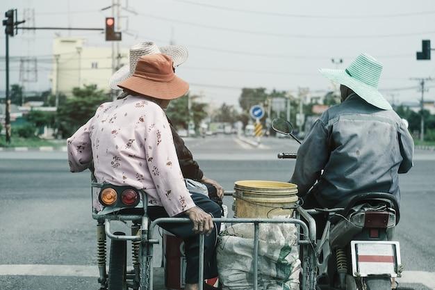 アジアの家族が赤信号で駐車してバイクを変更します Premium写真