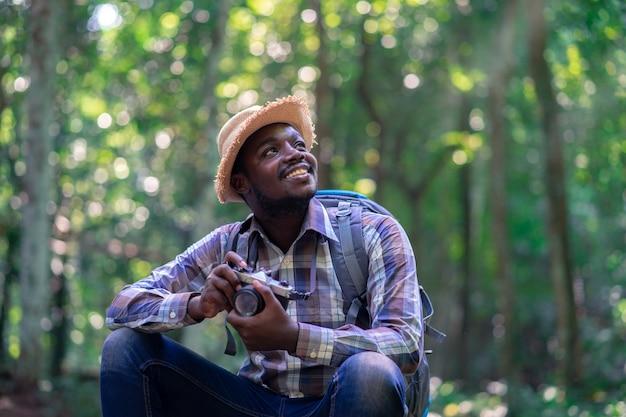 緑の自然林のバックパックでカメラを保持しているアフリカの自由人旅行者。 Premium写真