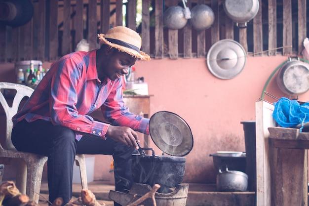 食べ物を調理する火を吹くために座っているアフリカ人 Premium写真