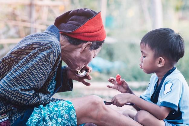 Азиатская старшая женщина и ее внук едят арбуз с улыбкой и счастливым Premium Фотографии