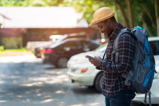 駐車場でスマートフォンを使用して、バックパックを保持している旅行者男 Premium写真