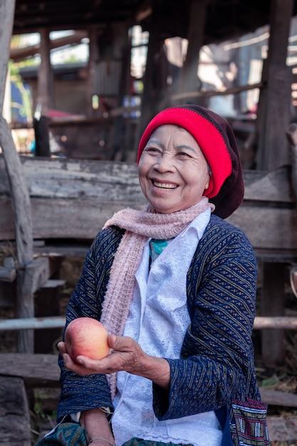 アジアの年配の女性を保持し、大きな笑みを浮かべて食用リンゴ Premium写真