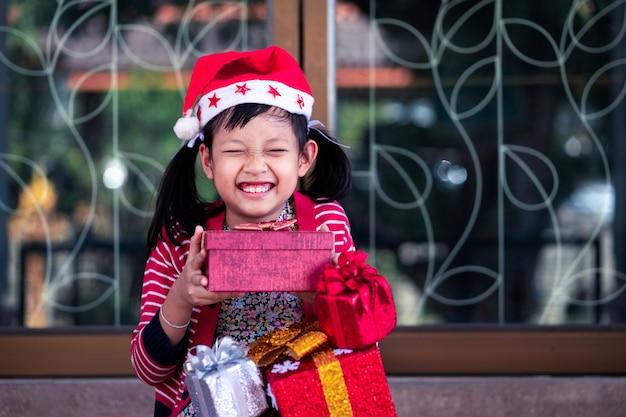 アジアのかわいい女の子が興奮してホリデーギフトを受け取る Premium写真