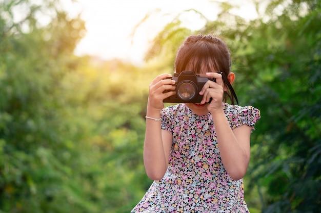 Азиатская девушка маленького ребенка держа камеру фильма и принимая фото Premium Фотографии