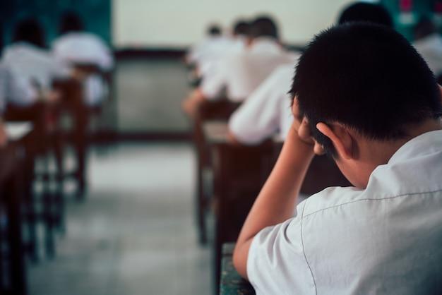 試験解答用紙を行う学生は、ストレスのある学校の教室で練習します。 Premium写真