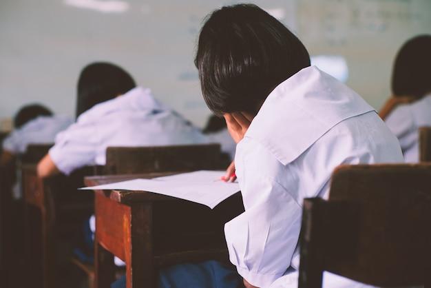 ストレスのある学校で生徒が試験の解答用紙を書き、読む Premium写真