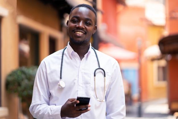 Африканский врач со стетоскопом, держа смартфон возле здания современной клиники больницы Premium Фотографии
