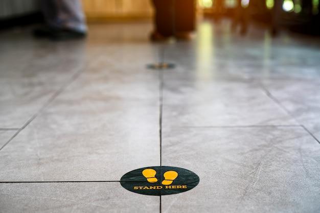 コーヒーショップの床にここに足の記号またはシンボルを立てる Premium写真