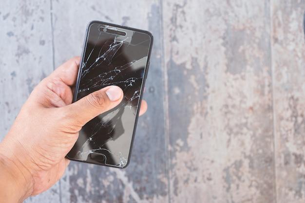 壊れたスマートフォンを持っている手 Premium写真