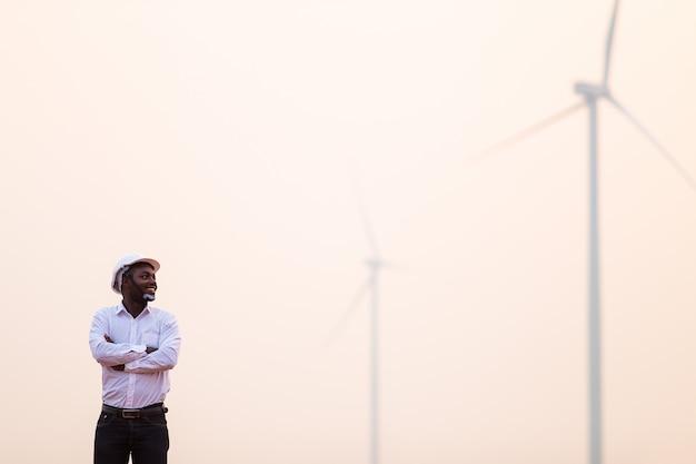 晴れた日に風力タービンに対してデジタルタブレットで立っている白いヘルメットを身に着けているアフリカのエンジニア Premium写真