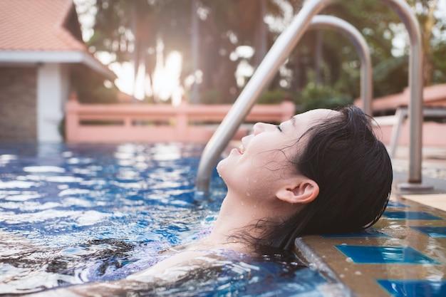 アジアの女性は幸福と感情をプールでリラックス。 Premium写真