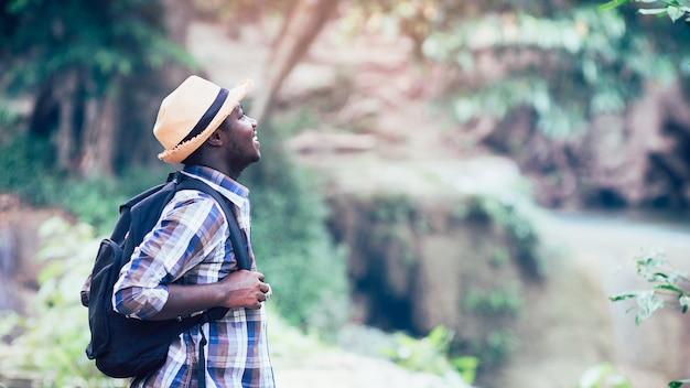 Африканский человек путешественник улыбаться и отдыхать в джунглях Premium Фотографии