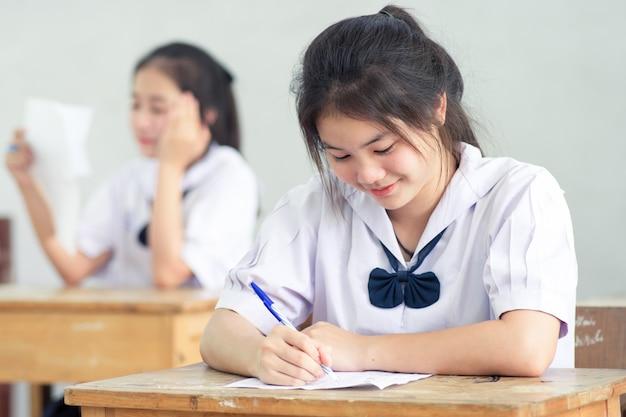 ストレスのない試験を読み書きする笑顔の若い女子生徒。 Premium写真