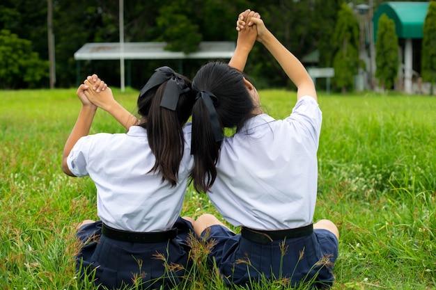 Студенты девушка обнимает в поле, концепция лучших друзей. Premium Фотографии