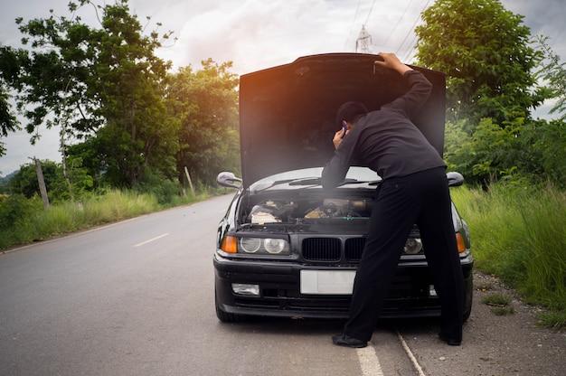 ストレスの実業家がスマートフォンを使用して壊れた車、エンジンを開くと喫煙を探しています。 Premium写真