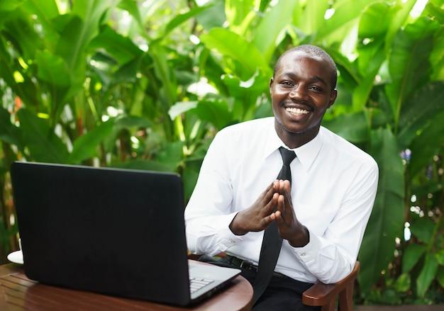 アフリカの実業家男性が支払う、訴えかけるように、ノートブックと幸せそうに笑っています。 Premium写真