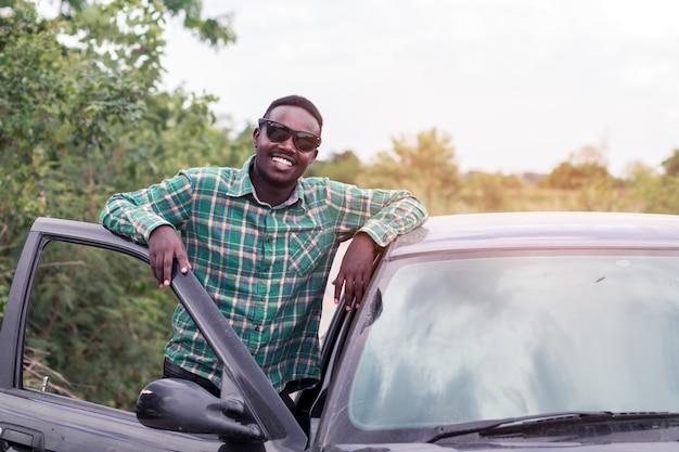 彼の車の開いたドアの近くの道に立っているアフリカ人。 Premium写真