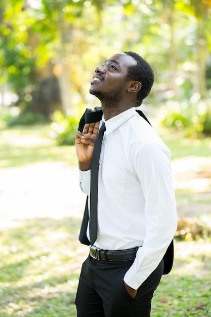 リラックスしたアフリカの実業家は、緑の自然とスーツを脱ぐ。 Premium写真