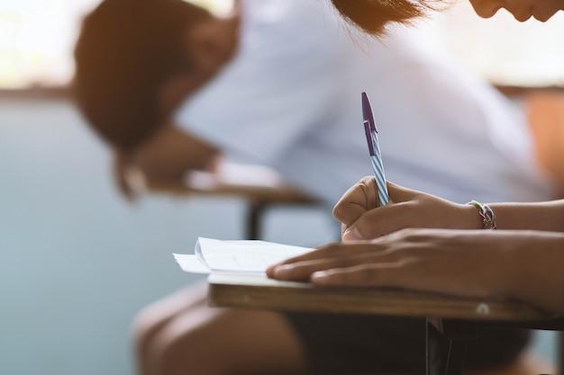 ペンを押しながら教育テストのストレスと教室で試験を受ける学生の手へのクローズアップ。 Premium写真