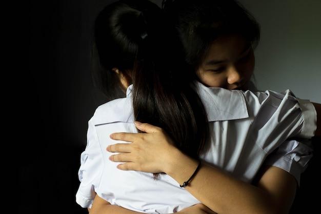 アジアの女子学生は彼女の親友に慰めを受け入れます。 Premium写真