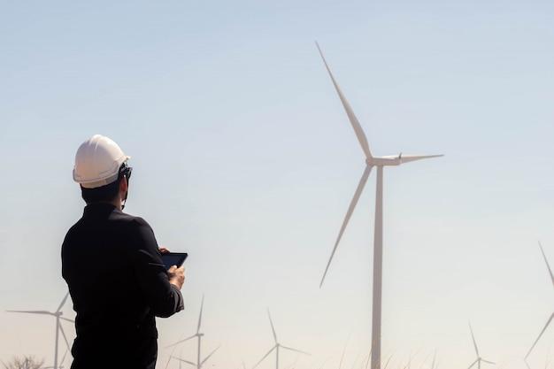 バックグラウンドで風力タービンとタブレットを保持しているビジネスアジア人の肖像画。 Premium写真