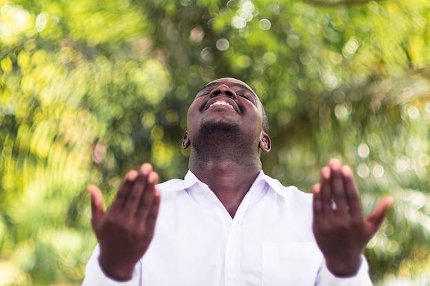 緑の自然と感謝の神を祈ってアフリカ人 Premium写真