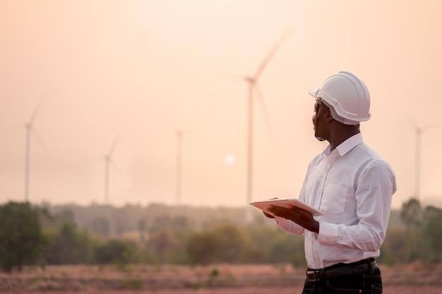 風力タービンに対してデジタルタブレットで立っている白いヘルメットを身に着けているアフリカのエンジニア Premium写真