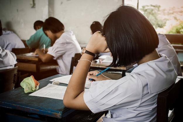 教室でストレスのある教育テストを行う制服の学生との試験 Premium写真