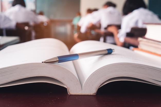 開いた古い本とペンは机の上に立ち、生徒は教室でストレスのある試験を受ける Premium写真
