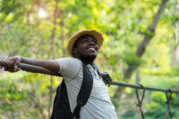Африканский путешественник человека с рюкзаком усмехаясь с зеленой предпосылкой природы. Premium Фотографии