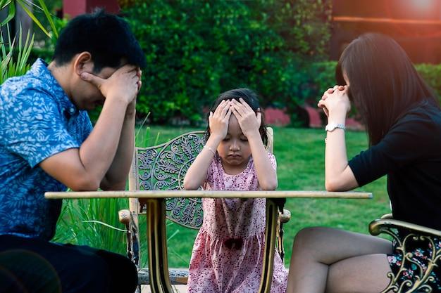 Азиатская маленькая дочь стресс и головная боль с отцом и матерью. Premium Фотографии