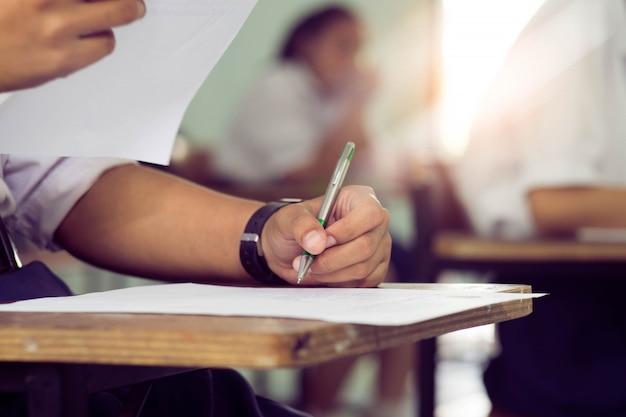 ストレスのある学校の教室で試験解答用紙を書いたり読んだりする生徒を閉じます。 Premium写真